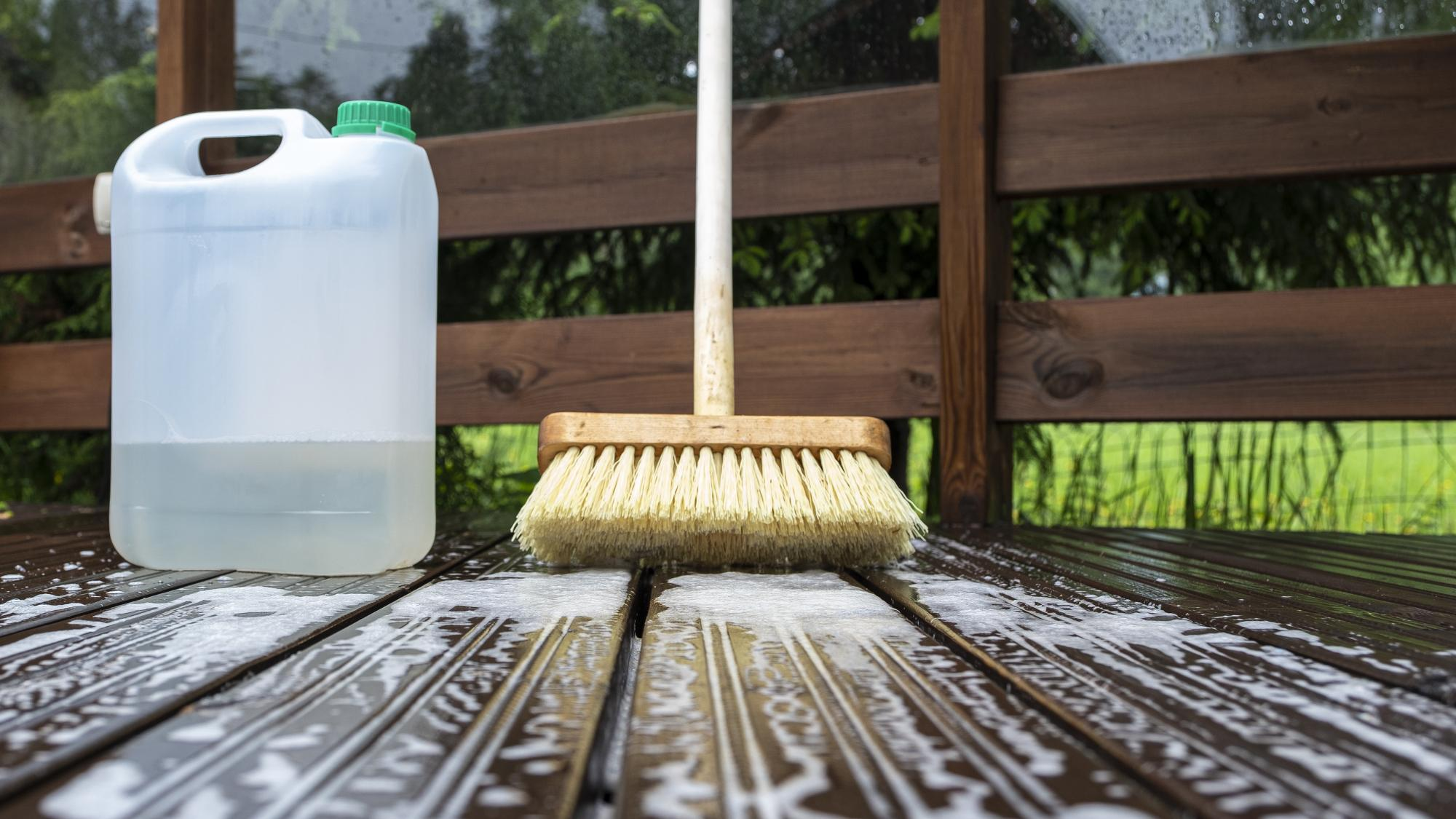 bottle of deck wash and a deck washing brush on a deck being washed