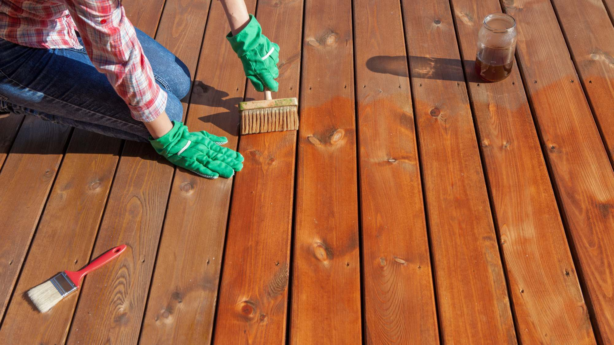 person applying transparent stain to a deck with brush