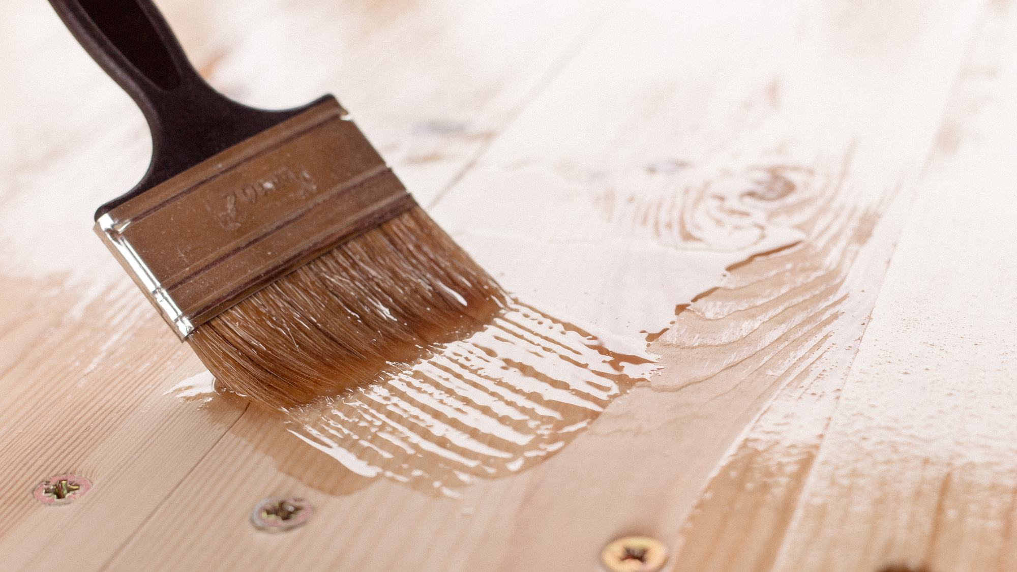 clear stain being applied on wood with brush