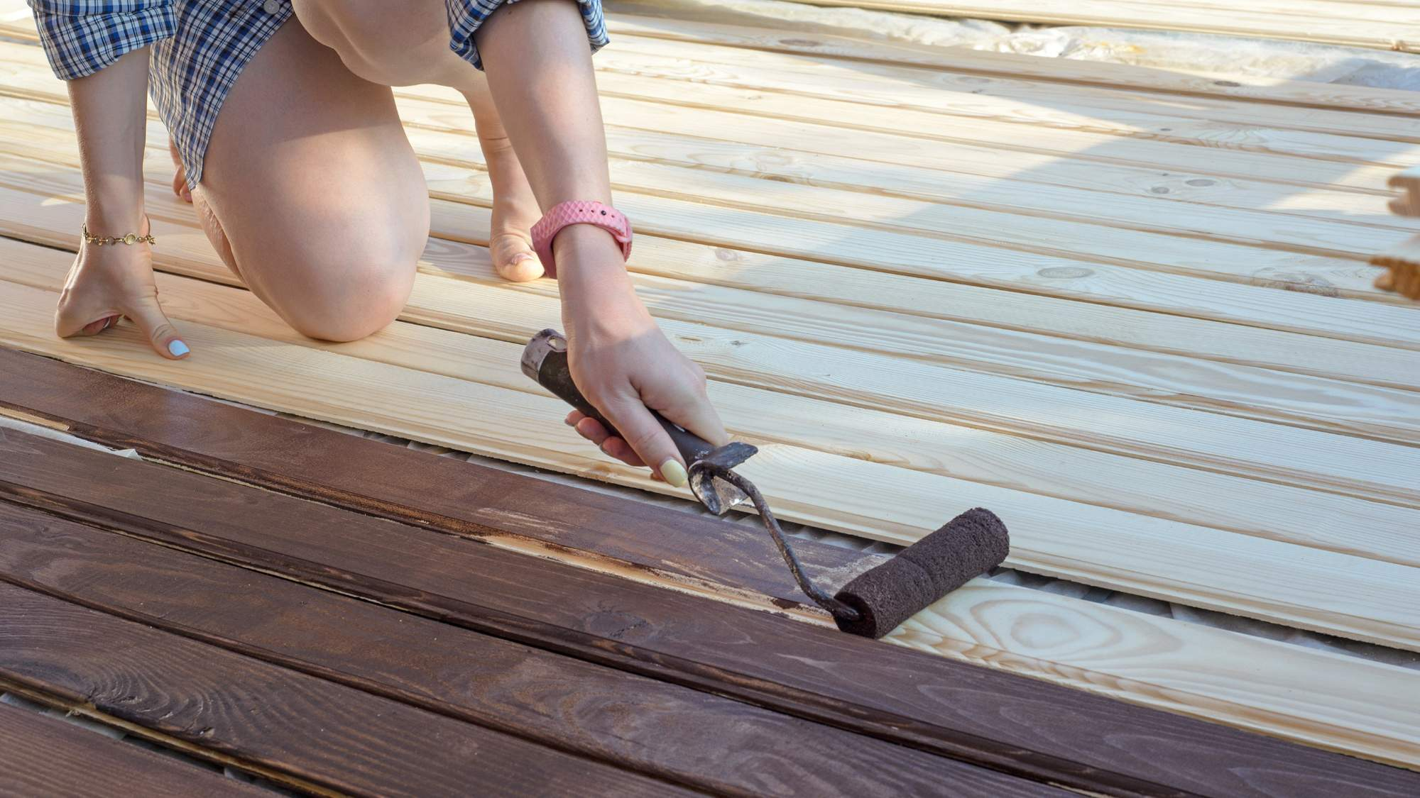 person applying semi solid stain on a deck with a roller brush