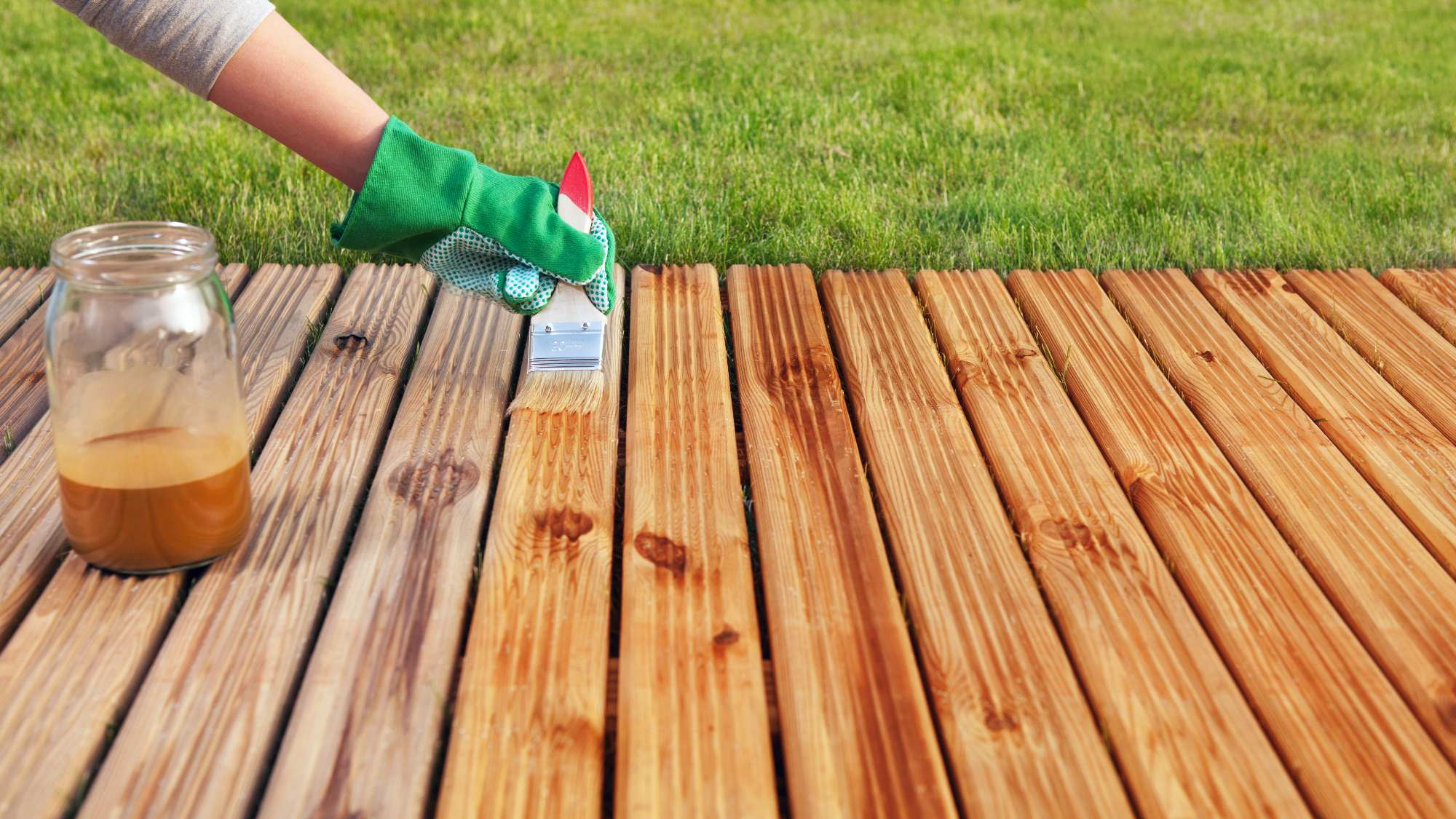 person applying semi-transparent stain to a deck with brush