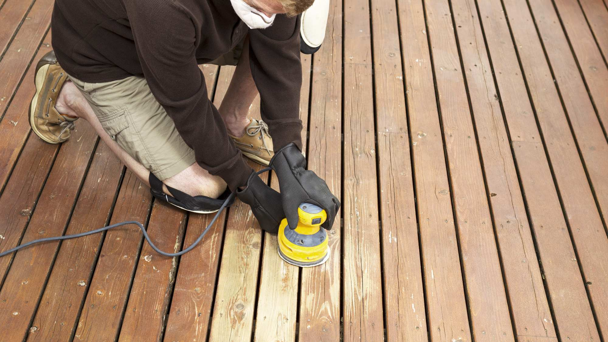 person sanding a deck with an electric sander