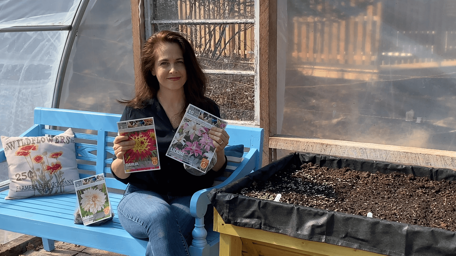 woman holding two gardening magazines with flowers on the cover