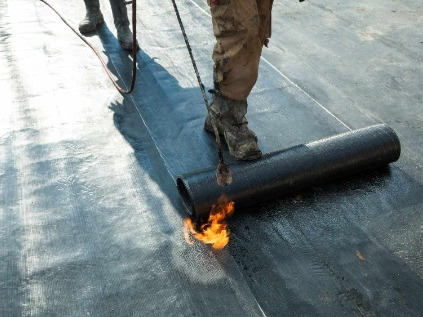 Person installing rolled roofing with torch