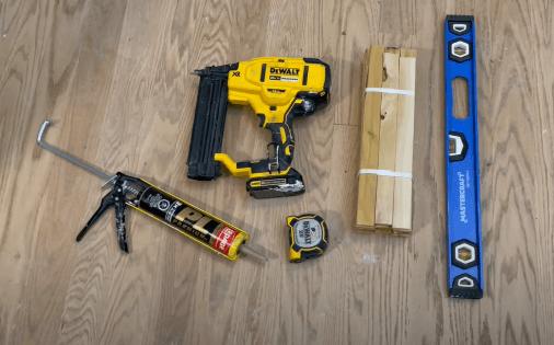 caulking in caulking gun, nailer, measuring tape, pack of shims, and level